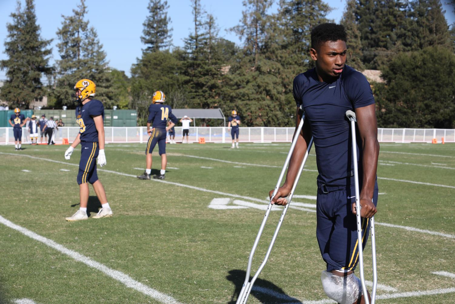 Junior Jaden Richardson on the sidelines after suffering a knee injury. Staff Photo: Parina Patel.