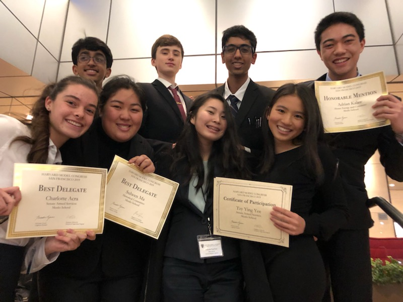 Menlo Model UN Club poses for a photo with their awards. Pictured from left: (above) freshman Vikram Seshadri, junior Jake Martin, sophomore Vivek Veluvali, senior Adrian Kalaw, (below) junior Charlotte Acra, junior Sulwen Ma, freshman Mitsuka Kiyohara, senior Tzy Ying Yee, (not pictured: senior Louis Levitan). Photo courtesy  of Charlotte Acra.