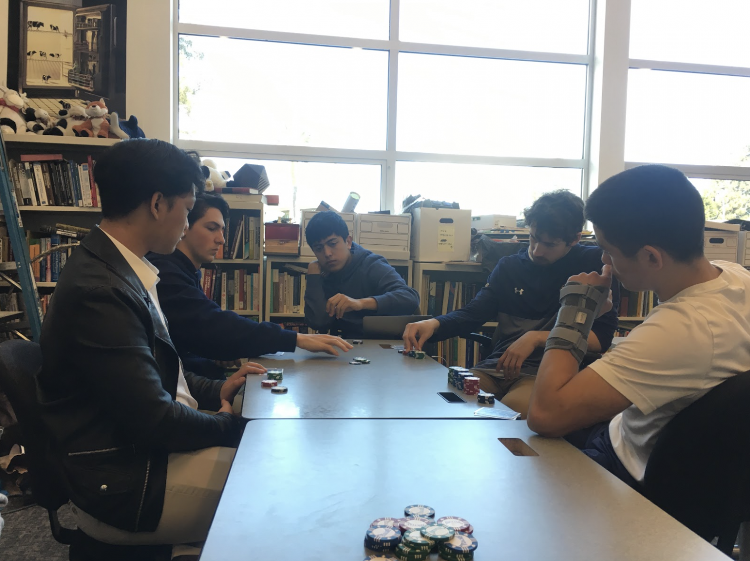 A group of seniors gather in the Neighborhood, a classroom in the back of the library, to play poker during lunch. Staff Photo: Shefali Sahai.