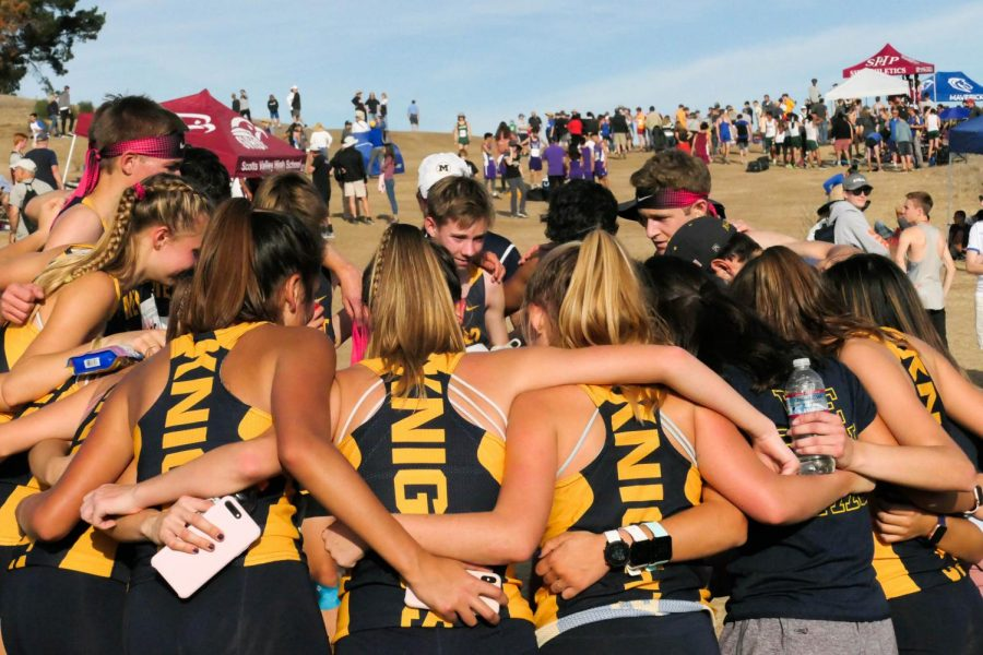 Coach+Jorge+Chen+congratulates+both+the+girls+and+boys+cross+country+team+in+a+huddle+after+learning+that+they+qualified+for+states.+Staff+Photo%3A+Bella+Guel.+