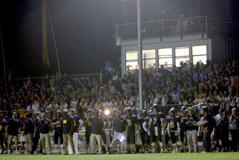 Students, coaches and the rest of the team support Menlo football players during the homecoming game in 2019. As a result of the the coronavirus pandemic, the team is now limited in how they can practice together, and gatherings without social distancing are prohibited. Staff photo: Emily Han.