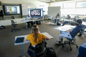 Menlo students and teachers sit socially distanced during the first round of hybrid learning in November 2020, with some students present in the classroom and some on Zoom for the lecture. Photo courtesy of Pete Zivkov.