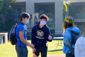 Seniors Alex Wang, Luke Yuen and Claire Ehrig greet each other on the quad during the Blue hybrid learning cohort's first week back on campus. Photo courtesy of Cyrus Lowe.