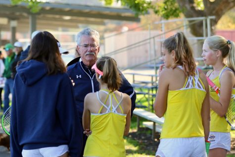 Menlo tennis coach Bill Shine coaches members of the varsity girls tennis team in between matches at the Stanford Invitational in 2019. Photo courtesy of Leon Yao.