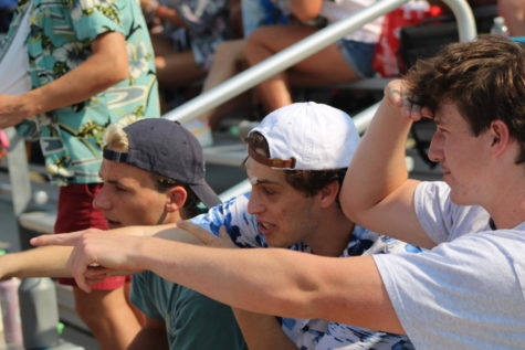 Menlo seniors, pictured left to right, Gregory Hilderbrand, Daniel Solomon and Henry Kearnan watch the first varsity football game of the season from the bleachers. Staff Photo: Alexa Friesel.