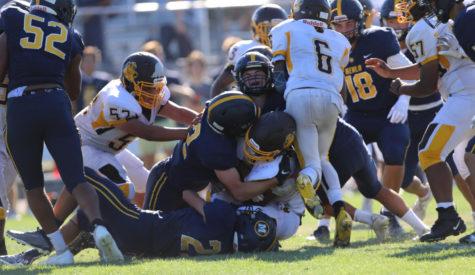 Menlo varsity football players Alec Jabal, Sam Randal and Alex Levitt combine for a tackle against Mission High School. Photo courtesy of Eli Housenbold.