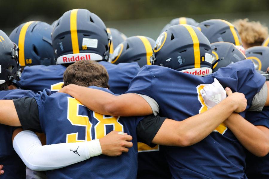 Menlo varsity football players huddle before their game against Terra Nova. Photo Courtesy of Eli Housenbold.