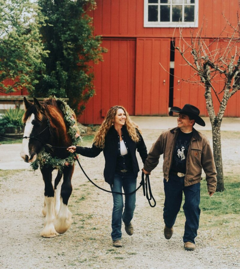 New Spanish teacher Patti Frias and husband Sal Frias walk with one of their horses on their 70-acre ranch. Photo courtesy of Patti Frias.